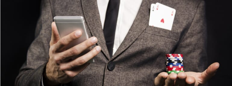 man in suit holding phone, playing cards, casino chips